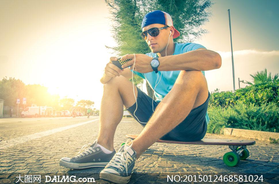 坐滑板上玩手机的帅哥摄影高清图片