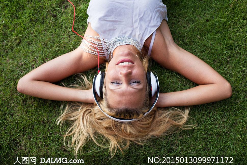 躺草坪上听音乐的美女摄影高清图片