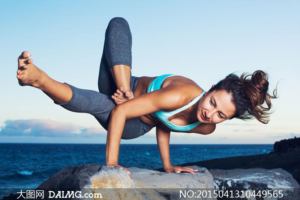 在海边岩石上做瑜伽的美女高清图片