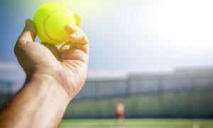 在手里的网球近景微距摄影高清图片