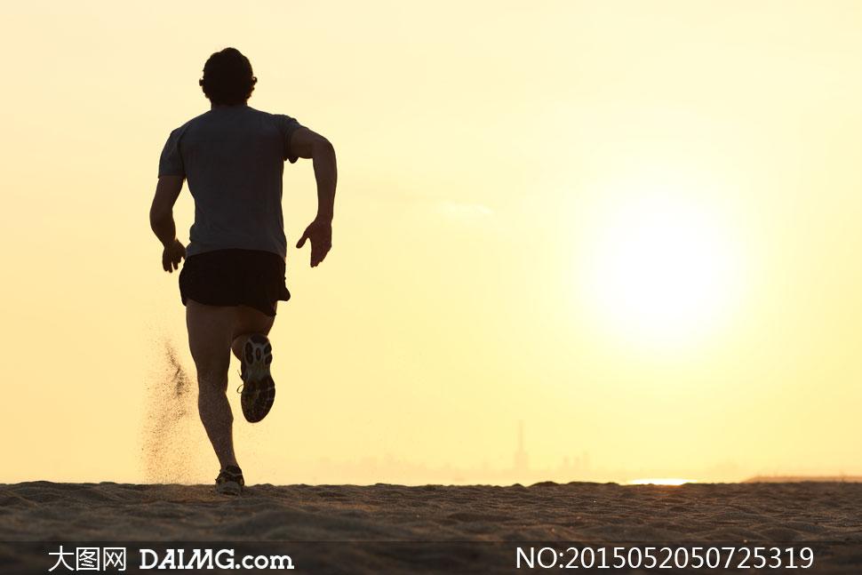 体育运动跑步背影尘土扬尘沙土沙子短裤短袖阳光天空逆光太阳光剪影图片