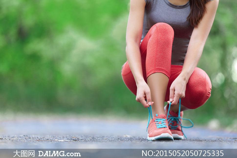 蹲下系鞋带的运动美女摄影高清图片