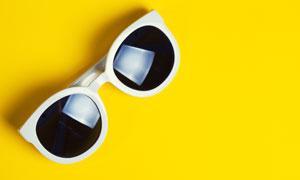 在黄色背景上的太阳镜摄影高清图片
