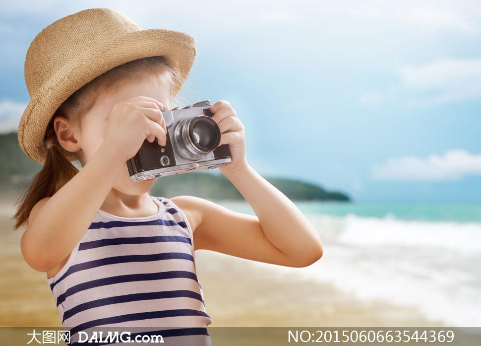 在海边沙滩上拍照的小女孩高清图片