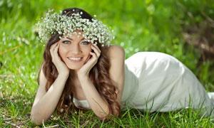 草地上托着下巴的长发美女高清图片