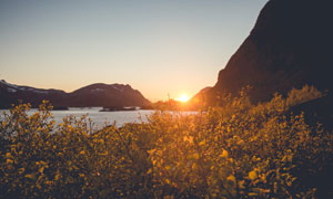 阳光照耀下的山石海水摄影高清图片