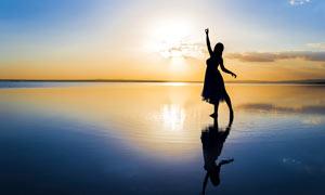 在海边翩翩起舞的美女摄影图片