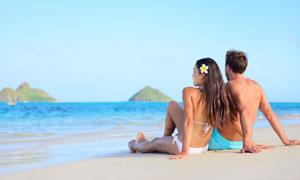 坐着海滩上的情侣男女摄影高清图片
