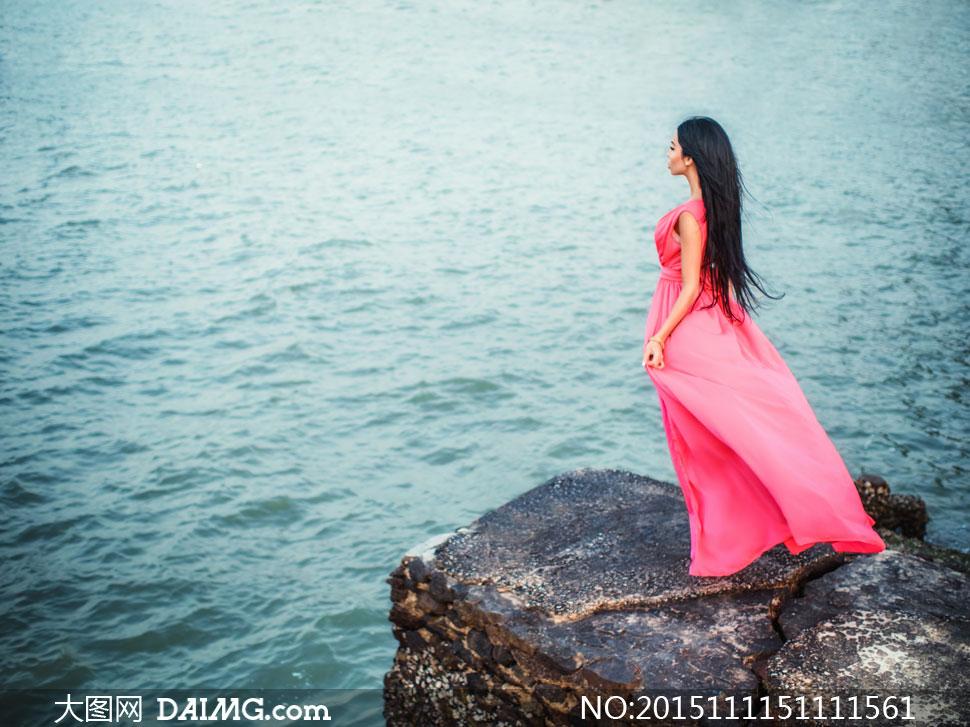 海边岩石上站着的美女摄影高清图片