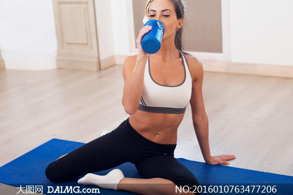蓝色瑜伽垫木地板房间室内坐着喝水膳食补充水分水杯