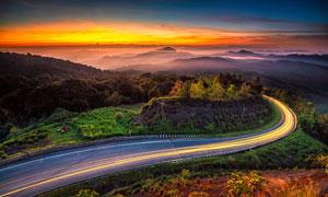 树木山峦道路与天边的霞光高清图片