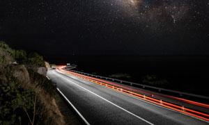 浩瀚星空与繁忙的公路夜景高清图片