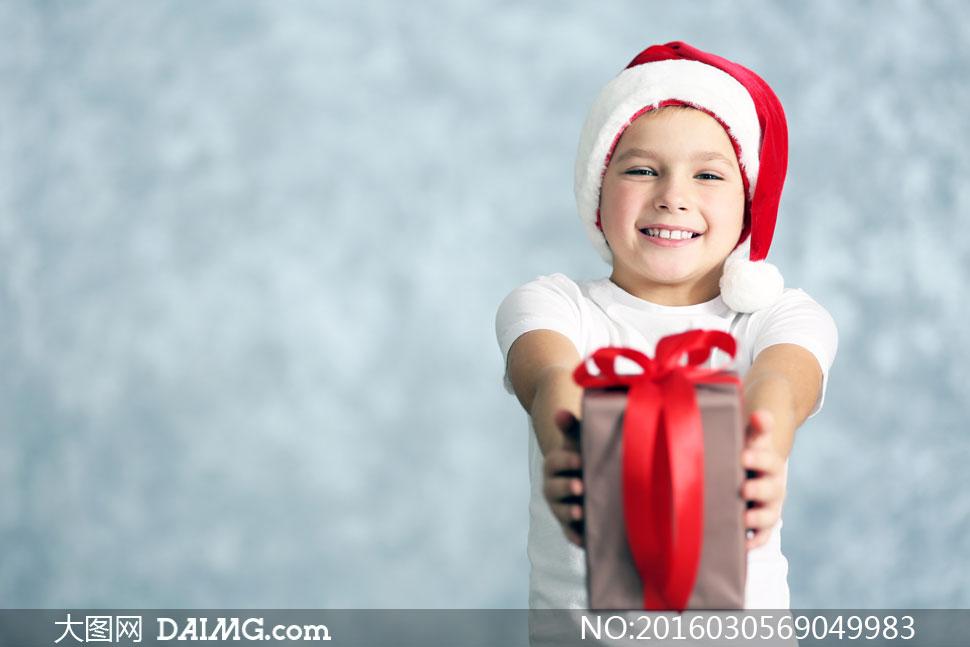 送礼物的圣诞装扮男孩摄影高清图片
