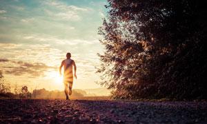 迎着阳光在慢跑的人物