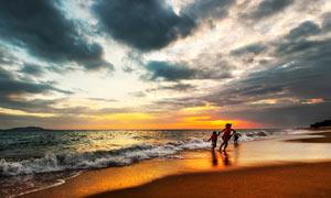 夕阳下的海边一家人美景摄影图片