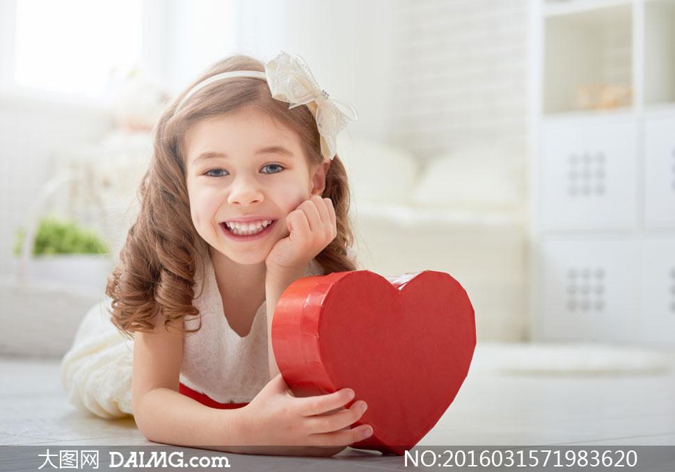手拿着礼物盒的可爱小女孩高清图片