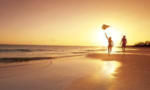 夕阳下海边沙滩奔跑的情侣摄影图片