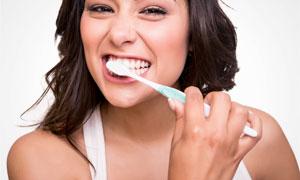 在使劲刷牙的黑发美女摄影高清图片
