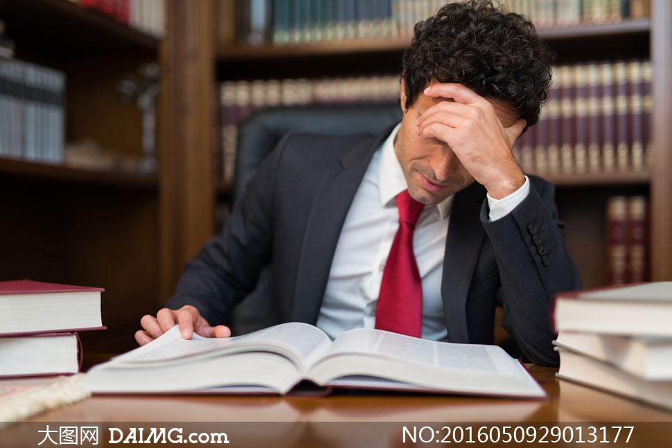 疲劳状态下看书的男人摄影高清图片