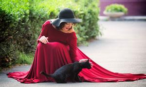 蹲下抚摸着黑猫的红裙美女高清图片