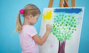 在画板前认真作画的小女孩高清图片