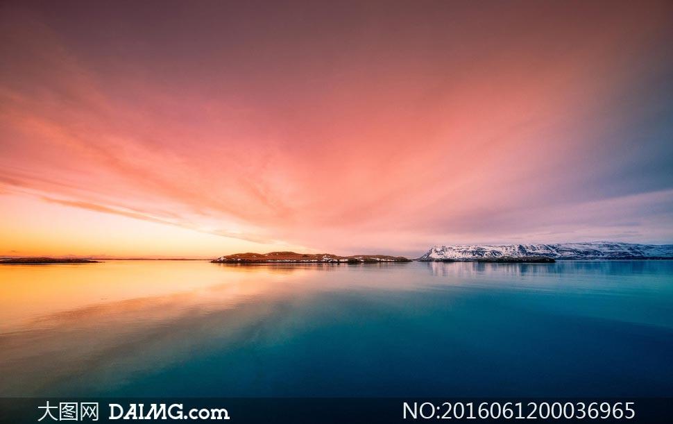 夕阳下的雪山和湖泊美景摄影图片