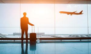 拉着行李箱的人物剪影逆光摄影图片