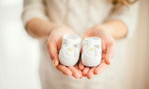 手里拿着小鞋子的孕妇特写高清图片