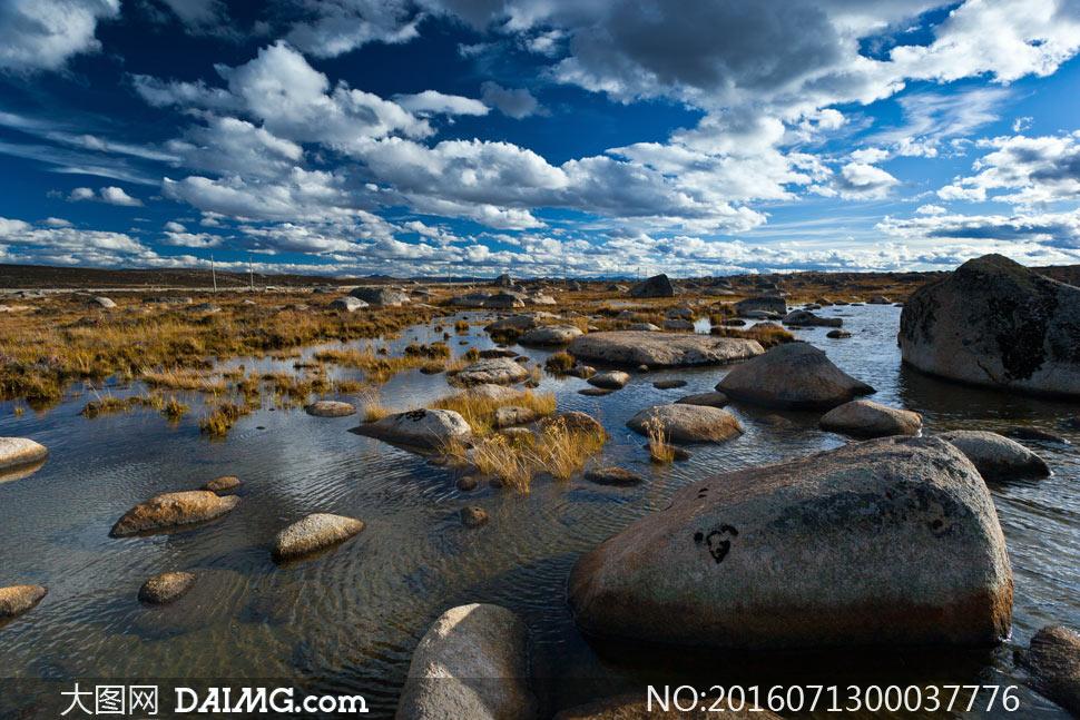 蓝天下的河边岩石摄影图片