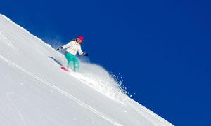 蔚蓝天空与坡上的运动人物摄影图片