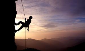黄昏傍晚攀岩运动人物剪影高清图片