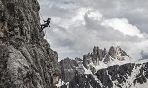 陡峭石壁上的攀岩人物摄影高清图片