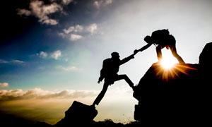 爬山中互相帮助的情景摄影高清图片