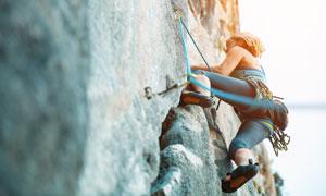 在往上攀爬的短发女子摄影高清图片
