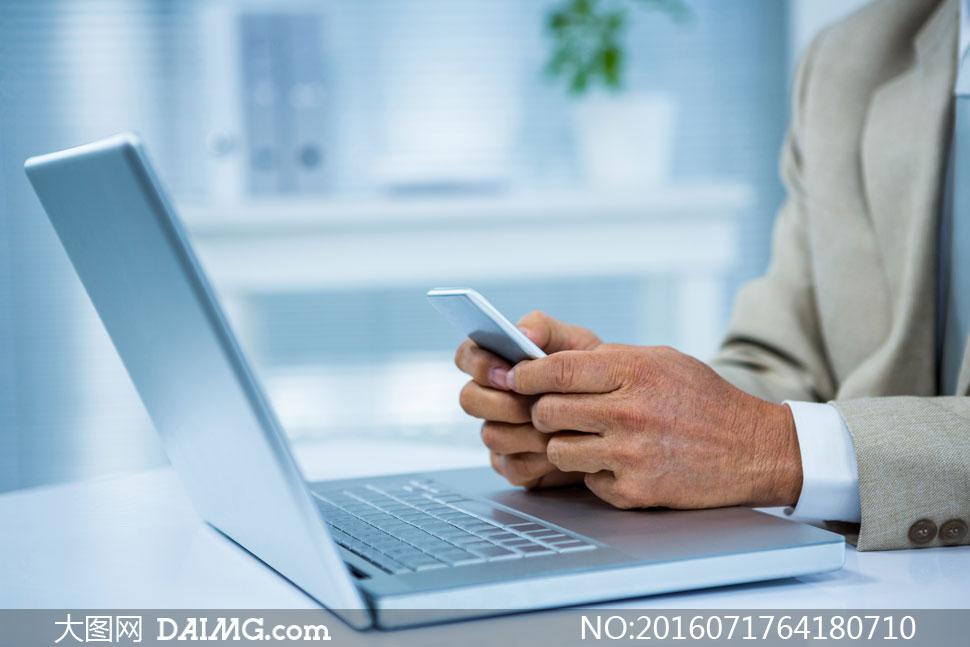 笔记本电脑与拿手机的人物高清图片
