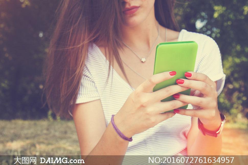 手拿着手机的美女特写摄影高清图片
