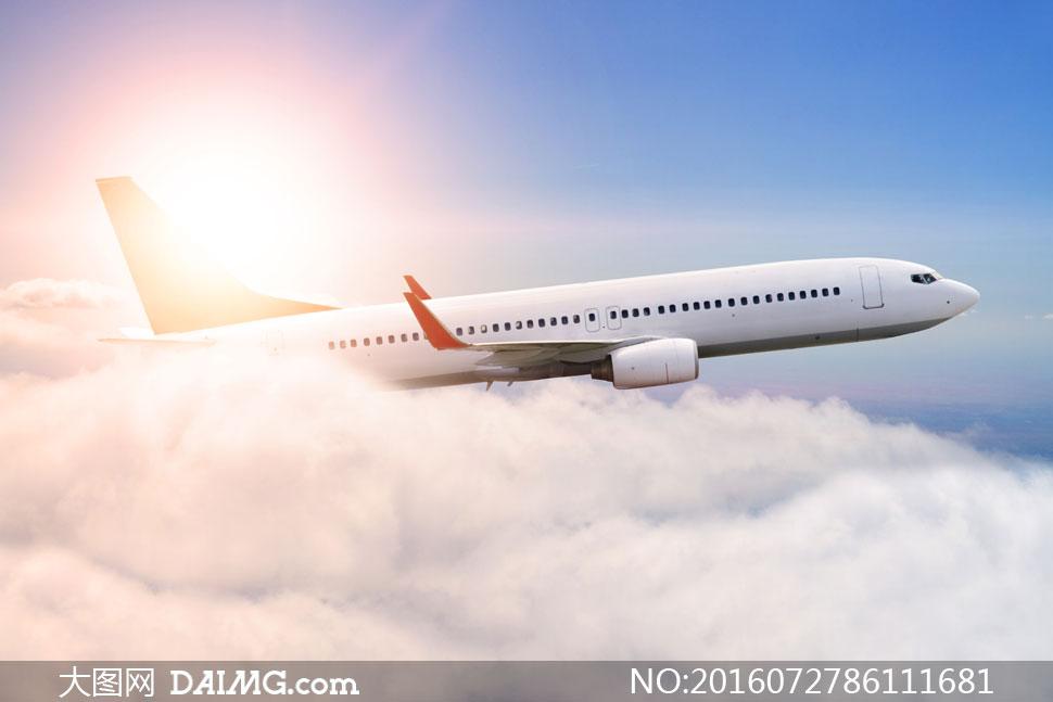 飞行在云层之上的飞机逆光摄影图片