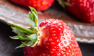 掉落在盘子外的大草莓摄影高清图片