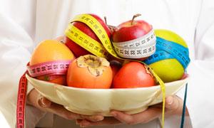 盘子里的苹果与柿子等水果高清图片