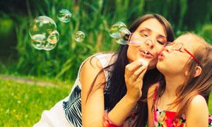 与女儿一起吹着泡泡的妈妈高清图片