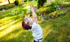 在玩着肥皂泡的小男孩摄影高清图片