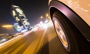 城市夜景与高速运转的车轮高清图片
