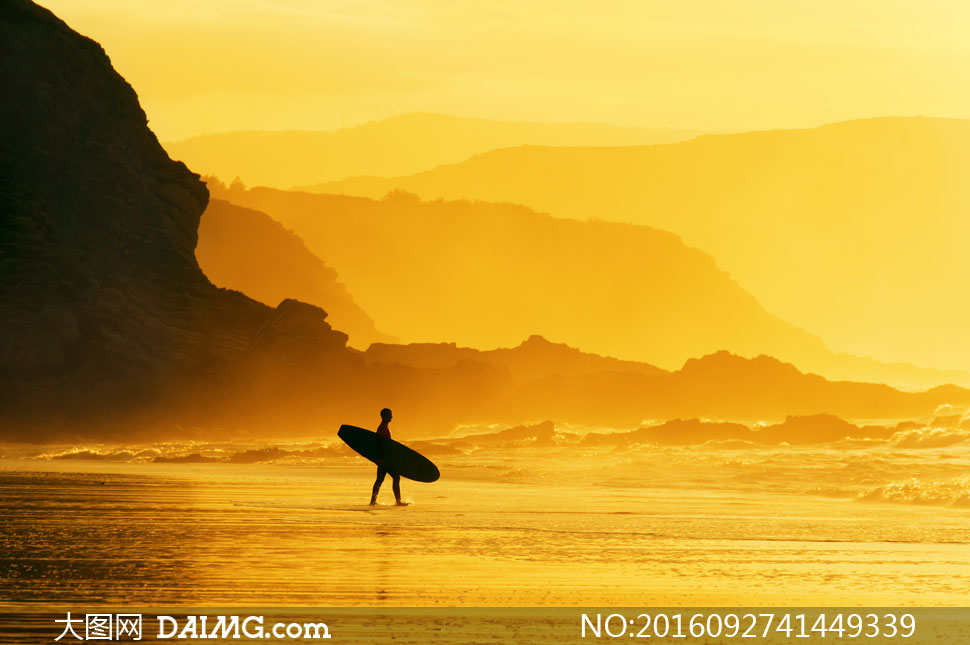 黄昏抱着冲浪板的人物剪影高清图片