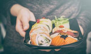 端在双手里的美味寿司摄影高清图片