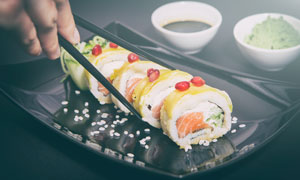用筷子夹着寿司的情景摄影高清图片