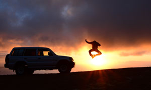 越野車與跳躍的人逆光攝影高清圖片
