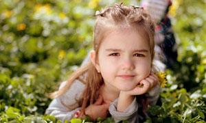 草地上托着下巴的女孩摄影高清图片