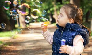 嘴巴吹着泡泡的小女孩摄影高清图片