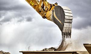 在往运土车上装土的挖掘机高清图片