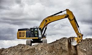 进行紧张挖土作业的挖掘机高清图片
